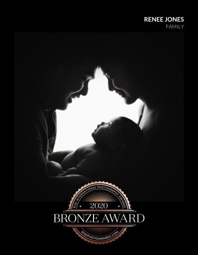2020 Bronze Award Rise International Photography Award Image Certificate for a black and white silhouette image of parents with their heads touching looking down at their baby.