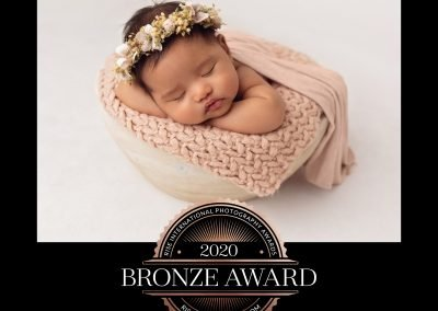 2020 Bronze Award Rise International Photography Award Image Certificate for a baby girl wrapped in pink asleep in a chin on hands pose in a white bowl prop