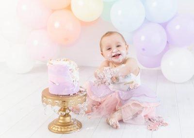 Little girl smiling during her pastel rainbow themed cake smash, purple cake smash, gold cake stand, pastel rainbow balloon garland