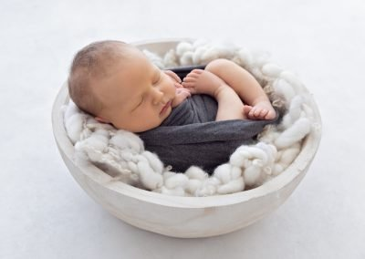 Baby boy in a gray wrap asleep on a white knitted layer blanket in a white bowl prop, side view, backlit