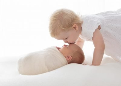 Toddler girl kissing her newborn sibling on the head, white tones, backlit side view image, newborn wrapped in cream