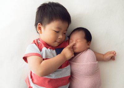 Toddler brother lying on his back with his newborn sister lying on his outstretched arm while he touches her nose with his finger, sibling portrait, back pose, overhead portrait