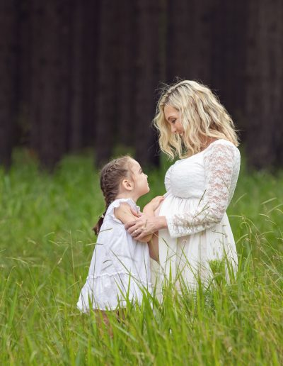 Mother and child maternity shoot, outdoors in a pine forest wearing white